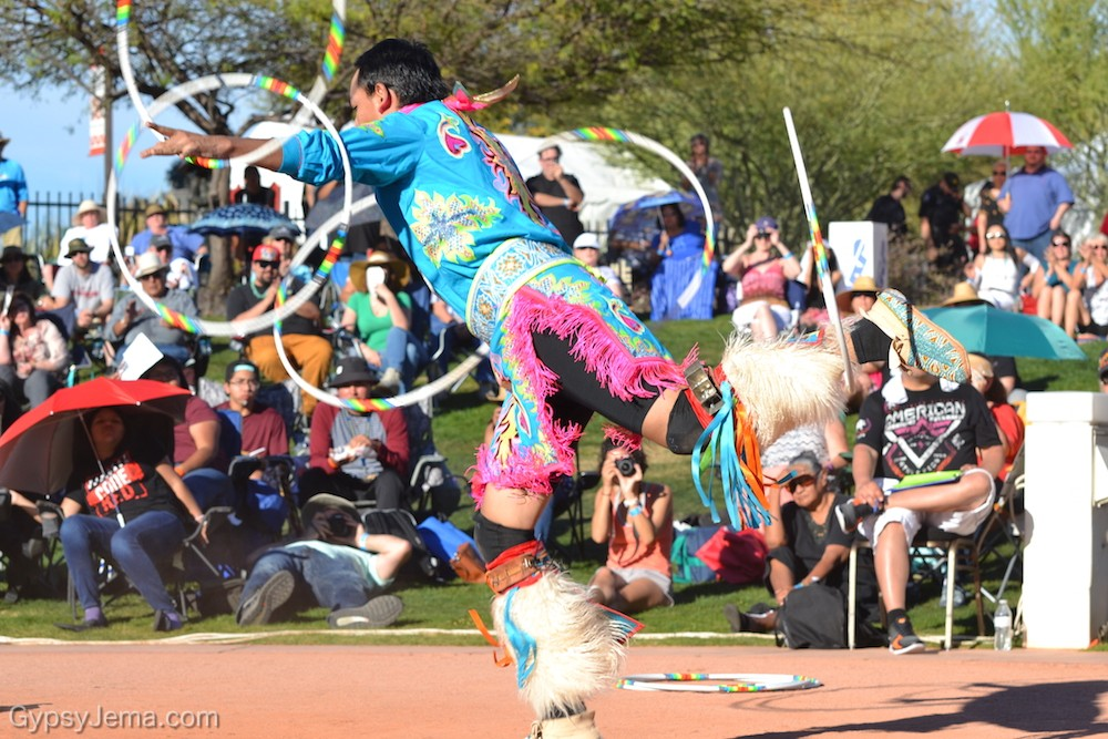 Using arms and foot to cirlce hoops at World Championship Hoop Dance Contest
