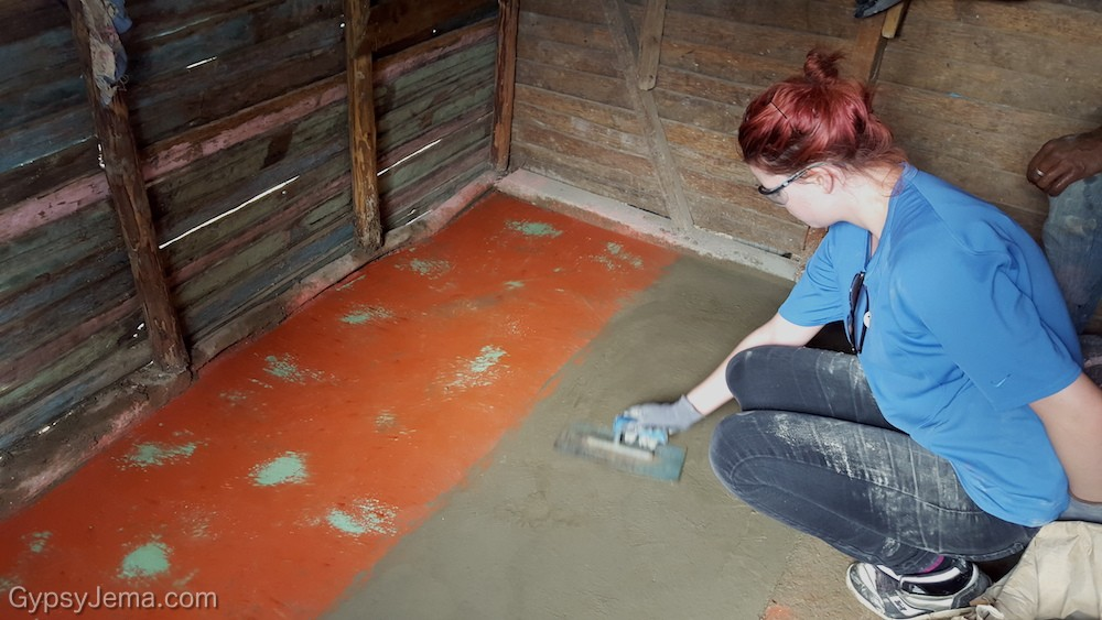 Teen working on concrete floors in community homes as part of Fathom Impact Travel